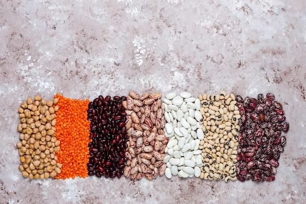 明るい石の背景に異なるボウルにマメ科植物と豆の品揃え。上面図。健康的なビーガンタンパク質食品。