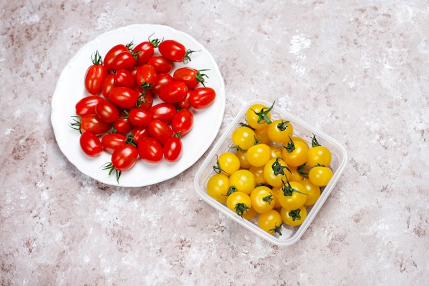 明るい背景にさまざまな色、黄色と赤のチェリートマトのチェリートマト