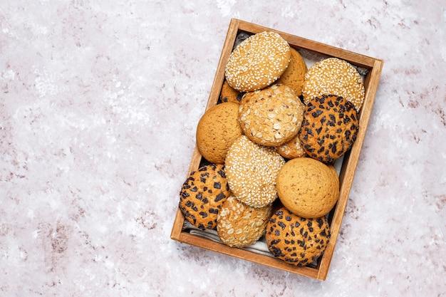明るいコンクリート背景の木製トレイに様々なアメリカンスタイルのクッキーのセット。ゴマ、ピーナッツバター、オートミール、チョコレートチップクッキーのショートブレッド。
