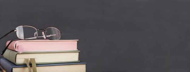 本と黒板にメガネで学校の背景に戻る