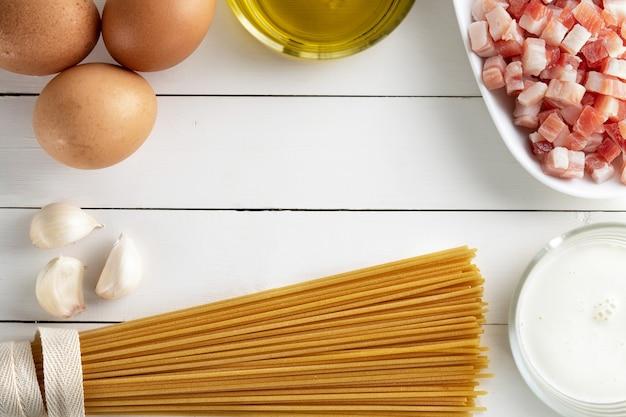 素朴な表面にイタリアのカルボナーラの食材を調理します。パスタ、パンチェッタのスパゲッティ