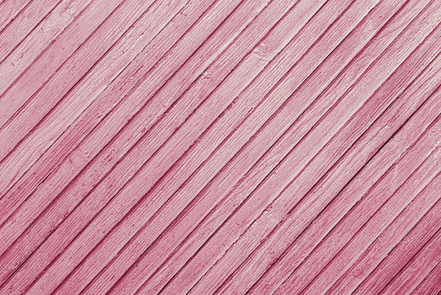 ひびの入ったペイントテクスチャと斜めに配置された木製の板のピンクのテクスチャ背景