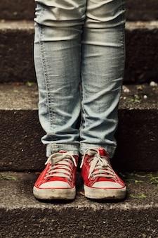 階段の上に立っているスニーカーとジーンズにクローズアップ