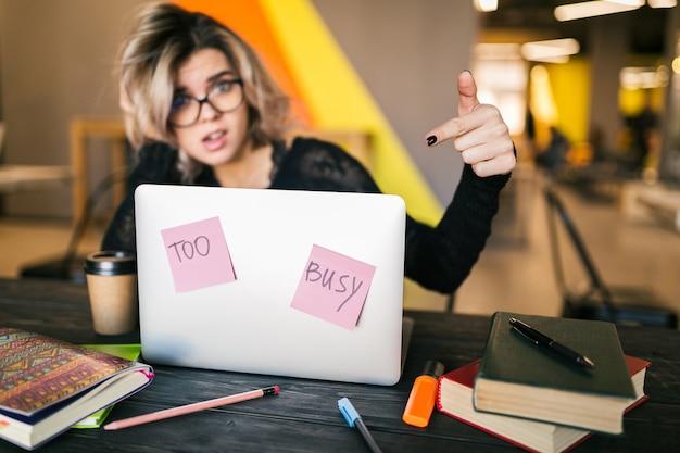 Молодая довольно занятая женщина, сидя за столом, работает на ноутбуке в совместном офисе, бумажные наклейки, в очках, согласие, студент в классе