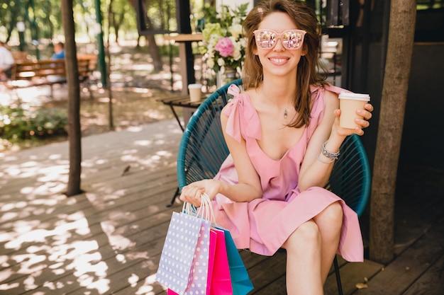 コーヒー、夏のファッションの服、ピンクのコットンドレス、トレンディなアパレルを飲むショッピングバッグのカフェに座っている若い笑顔幸せな魅力的な女性の肖像画