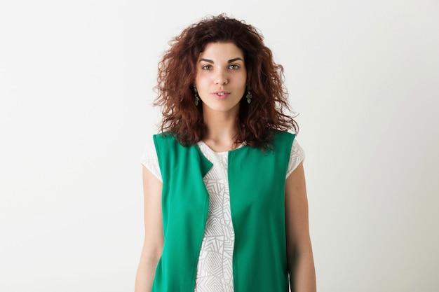 分離されたポーズの緑のシャツで巻き毛のヘアスタイルを持つ若い自然きれいな女性の肖像画