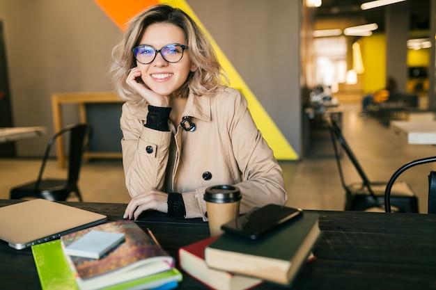 Портрет молодой красивой женщины, сидя за столом в тренче, работает на ноутбуке в офисе совместной работы, в очках, улыбаясь, счастливый, позитивный, на рабочем месте