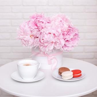 ピンクの牡丹、一杯のコーヒーとテーブルの上のマカロン