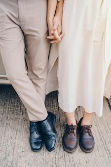 Крупный план влюбленных пар держа руки на поездке на заходе солнца.