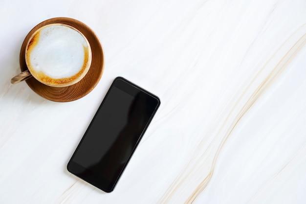 白い大理石のテーブルにラテコーヒーカップを持つ空の画面を持つモバイル
