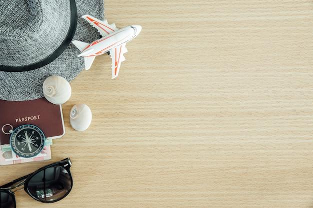 旅行の概念の背景。パスポート、コンパス、木製テーブルの上のアクセサリー