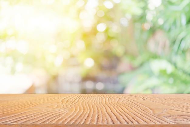 バックライト付きぼやけた自然と木製のテーブルの上から抽象的な背景。