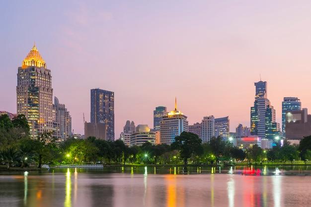 夕暮れ時のバックグラウンドでバンコクのビジネスセンター地区の高い建物とルンピニー公園の湖。