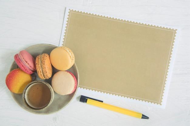 茶色の紙と白い背景の上の甘いデザートマカロンの空のページ。