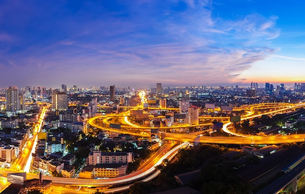 日没時の高速道路上の光の道とバンコク市。夕暮れ時の美しい街並み。