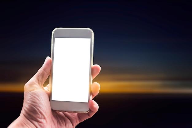 夕日を背景に空白の画面を持つ携帯電話を使用して手のクローズアップ。