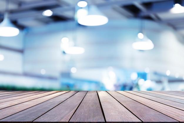 空スペースとぼやけているカフェの背景を持つ木の板。ショー製品の抽象的な背景。