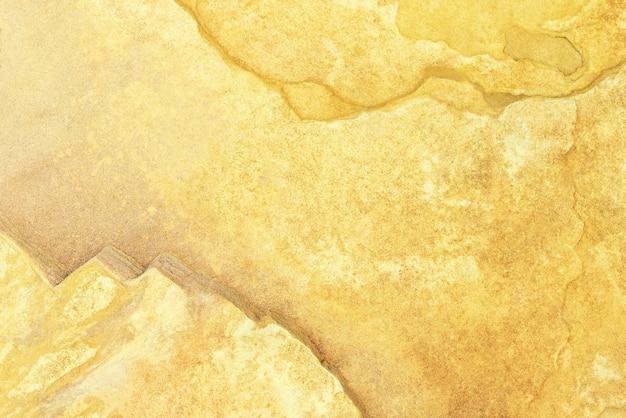 グランジとひびの入った古い黄色のコンクリートテクスチャ壁から抽象的な背景。