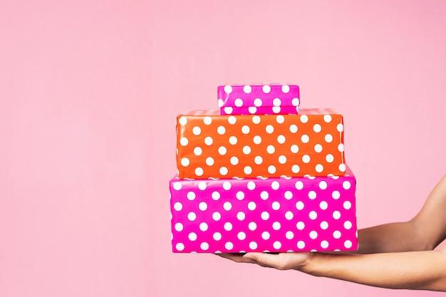 Крупный план рук держа подарочные коробки в розовой предпосылке. концепция праздника.