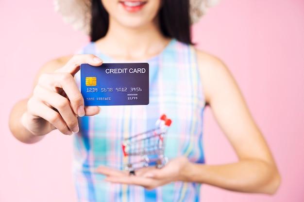 ショッピングのコンセプトピンクの背景にクレジットカードとショッピングカートを両手のクローズアップ。