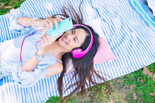 若い女性は、スマートフォンと幸せと庭の地面に横たわっているヘッドフォンで音楽を聴きます。