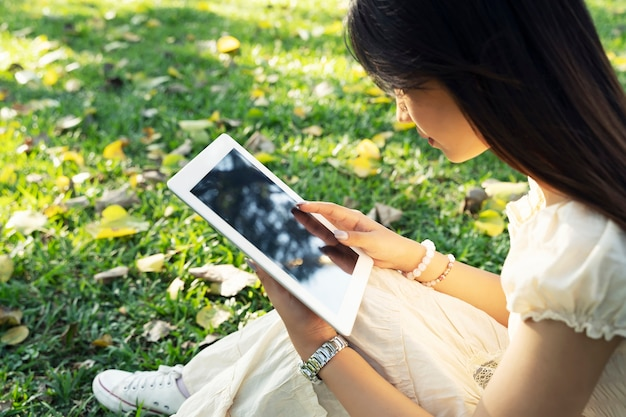タブレットを使用して庭で若い女性。人々の概念のための無線技術。