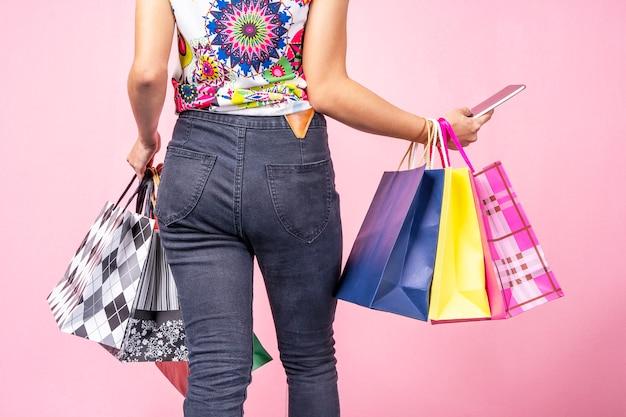 Крупным планом молодой женщины, держащей мобильный телефон и сумки