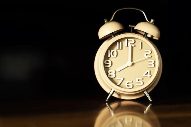 黒の背景を持つテーブルの上の目覚まし時計