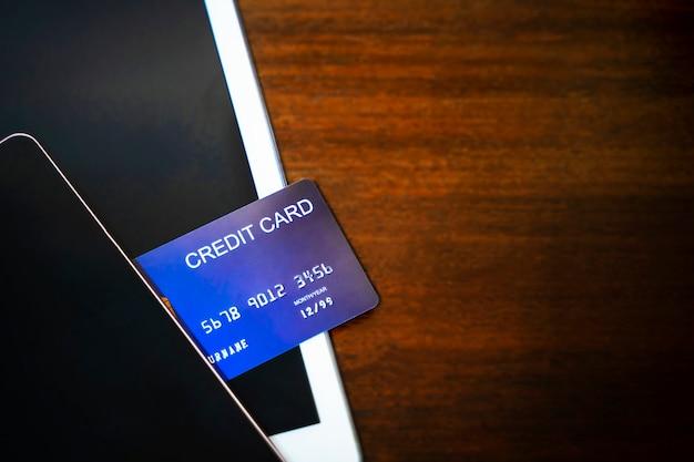 携帯電話とタブレットの木のテーブルにクレジットカード