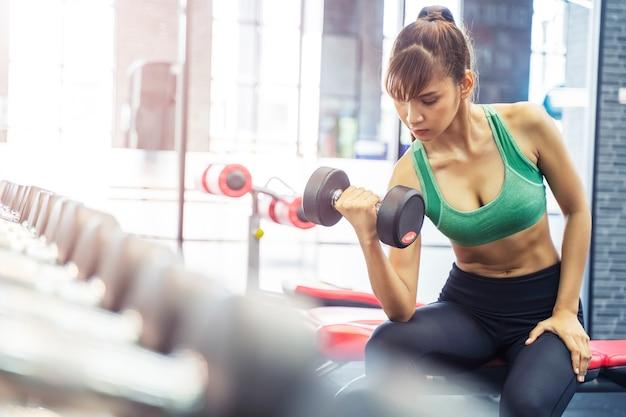 スポーツ女性のジムでダンベルトレーニング