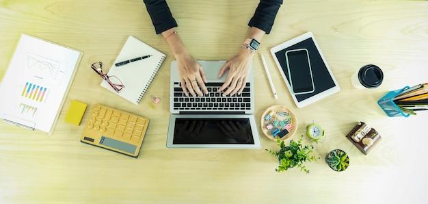 テーブルの上のノートパソコンとアクセサリーを扱うビジネス人々の手のクローズアップ
