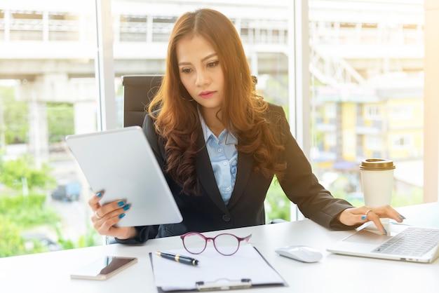 オフィスの机の上のラップトップで携帯電話を使用してビジネスの女性。