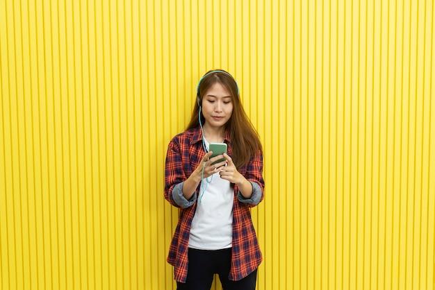 黄色の壁にモバイルとリスニング音楽を使用してカジュアルで若い女性。
