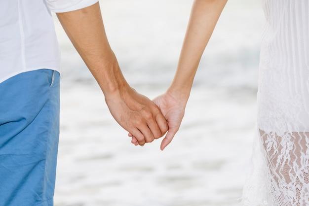 ビーチで一緒に手を繋いでいるカップル。