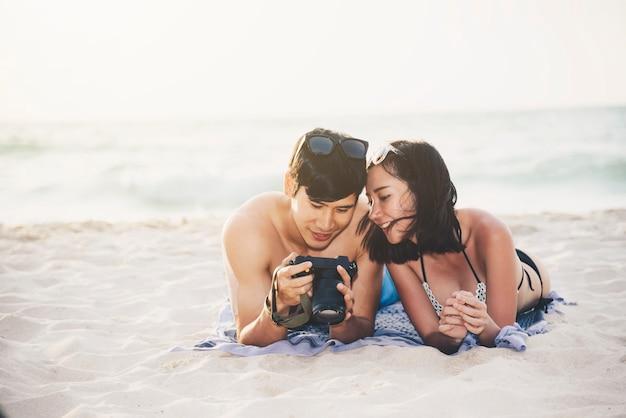 Пара счастья в романтической сцене на пляже на закате.