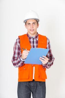 白い背景の上の手でチェックリストに立っている若いエンジニア男。