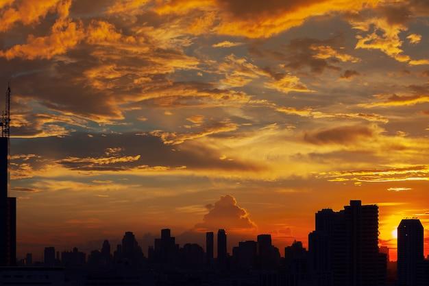 Закатное небо с силуэтами зданий в городе