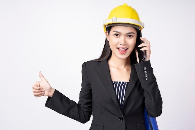 Портрет молодой женщины инженер, используя мобильный телефон с улыбкой
