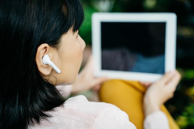Молодая женщина, используя беспроводные наушники и планшет
