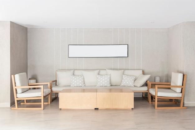 自宅でリラックスしてください。ソファと椅子、壁にフォトフレームが掛かっている。引き出し部屋