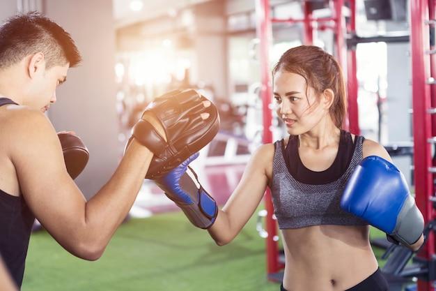ジムと女性の箱の手袋のスポーツのミットを持っている男トレーナー。フィットネスクラスターでボクシングの女性