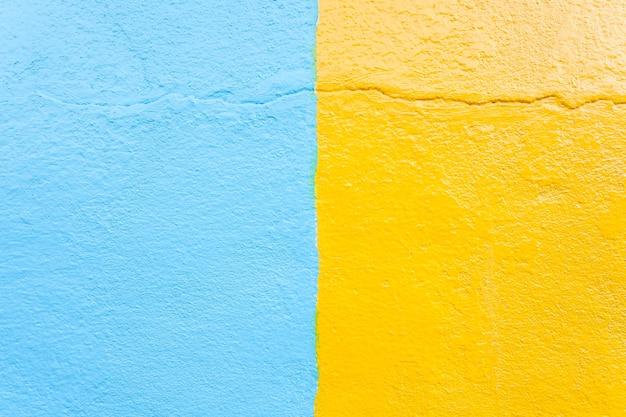 スタッコ青と黄色の壁のテクスチャの背景。