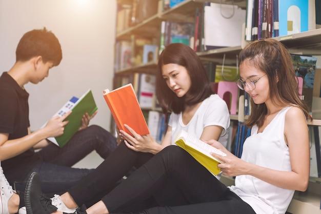図書館で読書する学生のグループ。教育コンセプト。