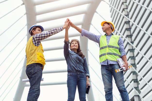 エンジニアたちは一緒に空に手を上げました。チームワークと成功のビジネスコンセプト。