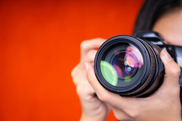 写真の背景のコンセプト。赤の背景にカメラを使用している写真家のクローズアップ。