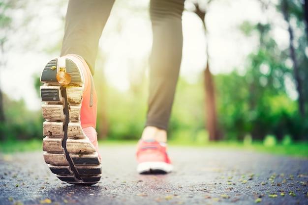 靴の上のクローズアップの上で走っている競技者の走者の足。空きスペースのあるジョギングシューズ