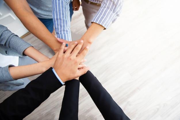 Концепция совместной работы. деловые люди стек рук для единства и команды. успех бизнеса.