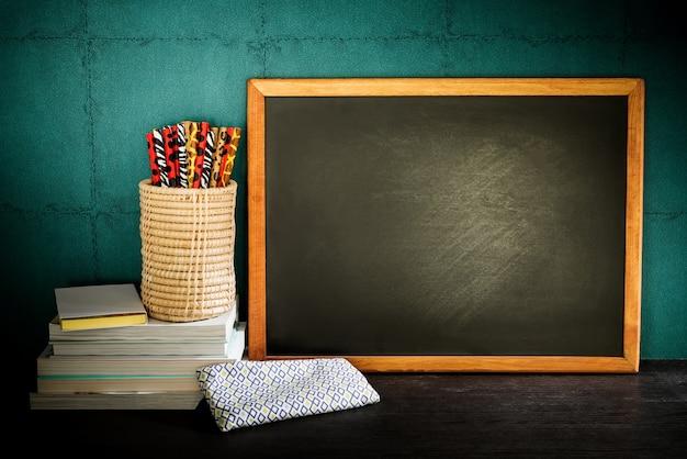 Натюрморт пустой доске и красочные карандаши с книгами на деревянный стол.