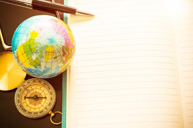 旅行の概念、ペン、コンパス、地球儀、そしてブログのエントリーのためのノートブックの空。