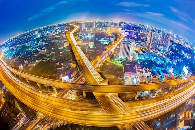 バンコク市内の高速道路のライトトレイル。近代都市の交通と交通の高層ビル。